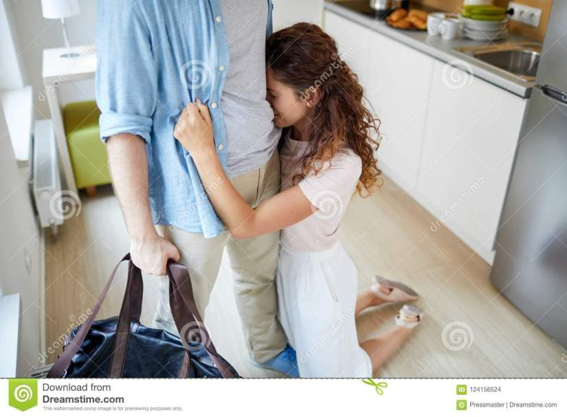 begging-not-to-leave-young-women-crying-standing-knees-her-leaving-husband-embracing-him-124156524.jpg